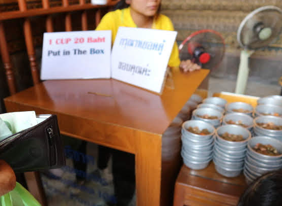 Cup of coins at Reclining Buddha Thailand.