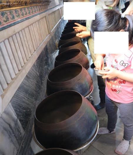 Coins pot at Reclining Buddha Bangkok Thailand.
