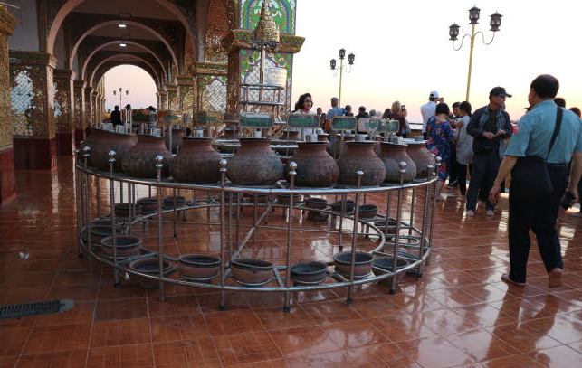 The pots filled with coins at Mandalay hill temple.
